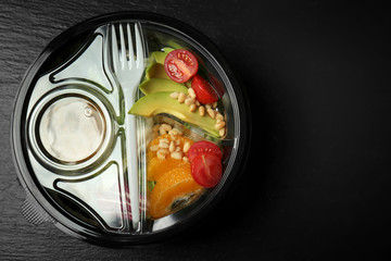 Plastic container with delicious food on dark table