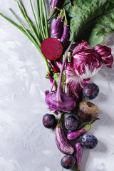 Assortment raw organic of purple vegetables mini eggplants, spring onion, beetroot, radicchio salad, plums, kohlrabi over gray concrete background. Top view with space