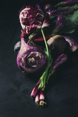 Assortment raw organic of purple vegetables mini eggplants, spring onion, beetroot, radicchio salad, plums, kohlrabi, flower salt over dark metal background. Close up with space