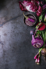 Assortment raw organic of purple vegetables mini eggplants, spring onion, beetroot, radicchio salad, plums, kohlrabi, flower salt over dark metal background. Top view with space. Food frame