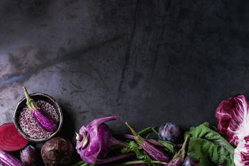 Assortment raw organic of purple vegetables mini eggplants, spring onion, beetroot, radicchio salad, plums, kohlrabi, flower salt over dark metal background. Top view with space. Food frame