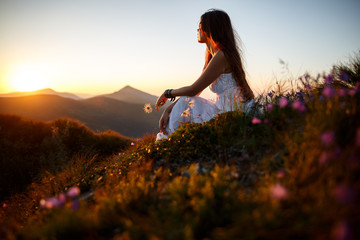 Beautiful woman in a long white dress in the mountains. Young woman sitting on a rock. Hair blowing in the wind