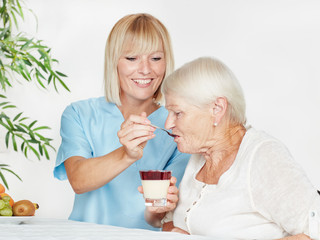 Carer spoon-feeds a elderly person