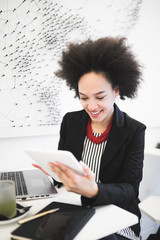Confident and smiled cute Afro american business woman sitting in modern cafe and using her laptop or tablet.