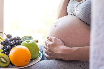 A pregnant woman with belly holding a plate with fruits. Concept for weight control and healthy eating during pregnancy
