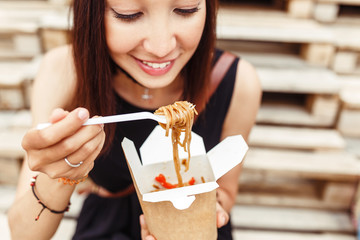 Beautiful woman are eating asian fast food from takeaway box. Delicious Wok noodles