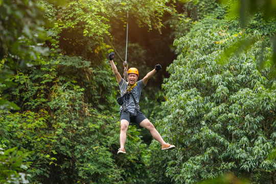 Freedom Man Tourist Wearing Casual Clothing On Zip Line Or Canopy Experience In Laos Rainforest, Asia