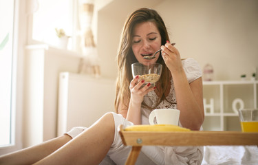 Young woman having breakfast in bed. Young woman eating cereal.