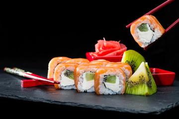 traditional Japanese cuisine. Process of eating sushi rolls with salmon, cream cheese, rice and kiwi on dark background, selective focus
