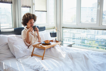 Beauty woman sitting on bed, eating breakfast