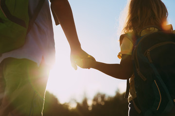 little boy and girl with backpacks holding hands at sunset