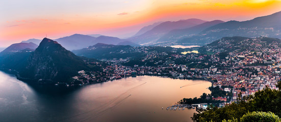 Aerial view of the lake Lugano surrounded by mountains and evening city Lugano on during dramatic sunset, Switzerland, Alps. Travel Wall mural
