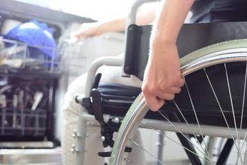 Junge Frau im Rollstuhl bedient Geschirrspülmaschine
