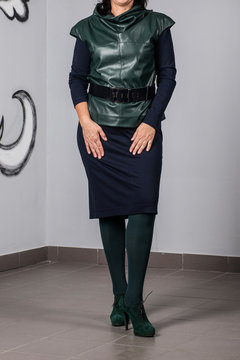 Beautiful woman posing in green leather vest and skirt. Details of women's clothing.