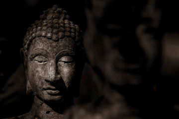 Head of Buddha statue in the dark, the dark side of Buddha, antique and ancient statue of buddha