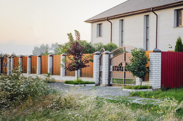 A brown fence made of polyprofile with a canopy in a modern style with brick columns, the design of a country house.