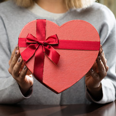 woman received beautiful gift box with present in the shape of heart. For Mothers Day, Valentines Day and Birthdays