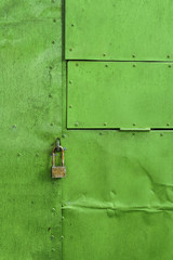 Green painted aluminium sheet background with rivets and lock