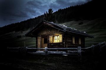 Almhütte mit erleuchtetem Fenster