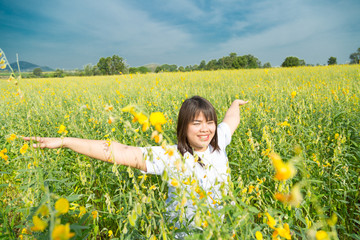 asian young  chubby women is raising arms to the sky in yellow field at summer, Thailand