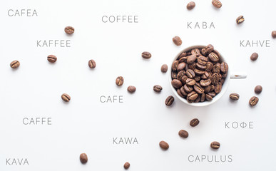 Bright coffee beans in a cup and spread over a light background with coffee spelled in different languages, representing an international component to coffee consumption.