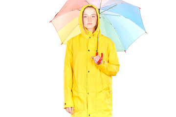 Studio portrait of teenage girl wearing yellow raincoat and holding open colorful umbrella isolated on white