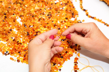 Amber. The process of making beads from sun stone with the help of thread and needle. Hands of the master select pieces of amber for jewelry. Production of amber beads