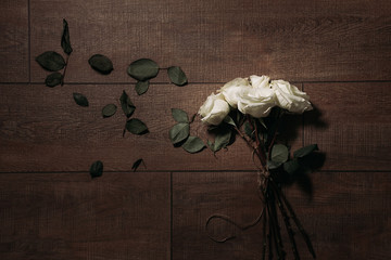 Overhead view of bunch of white roses with leaves on hardwood floor