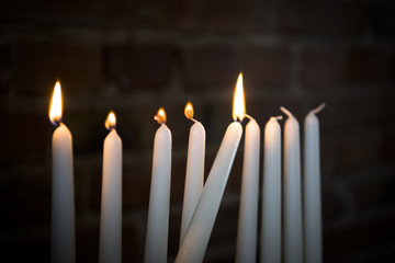 Close-up of lit candles in darkroom against brick wall during Hanukkah