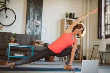 Woman doing yoga in loft apartment with laptop
