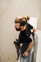 Man leaning against skateboard