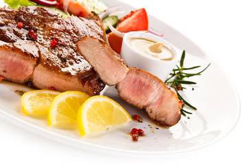 Roast steak with vegetables on white background