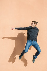 Teenage boy jumping in front of a wall.