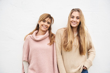 Mother and daughter standing against white wall