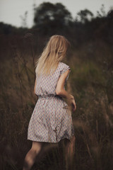 Unrecognizable female walking in autumn field