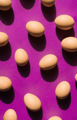 Purple background with raw/boiled eggs.