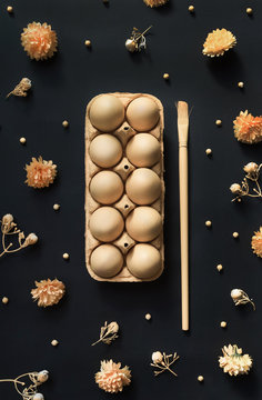 Pack of eggs with brush and decorative elements on stylish black background.