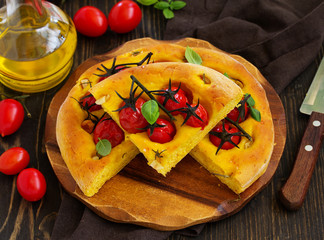 Focaccia of pumpkin dough with tomatoes, rosemary and garlic.