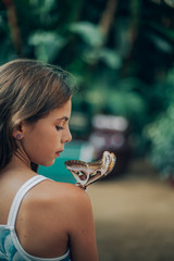 Portrait of young girl with real butterfly