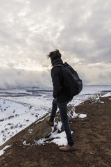 Man looking at winter landscape from the top of a mountain