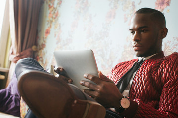 Stylish Young Black Man Sitting on Sofa and Reading on Tablet