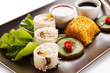 Roast, stuffed chicken roulade with rice and vegetables on white background