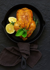 Baked whole chicken with lemon and herbs.