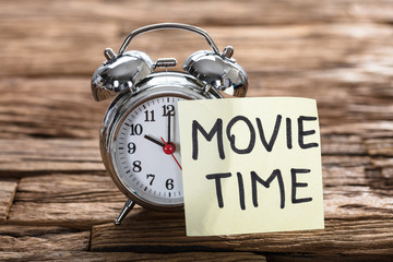 Alarm Clock With Movie Time Text On Sticky Note