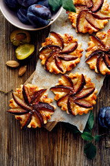 Plum cakes with cinnamon  on a wooden table, delicious dessert with  puff pastry and fruits, top view