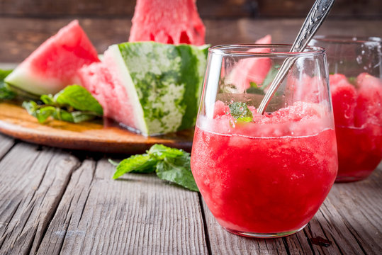 Summer fruit desserts, frozen cocktails. Ice cream granite from watermelon with mint, in portioned glasses, with slices of watermelon. On old rustic wooden table Copy space