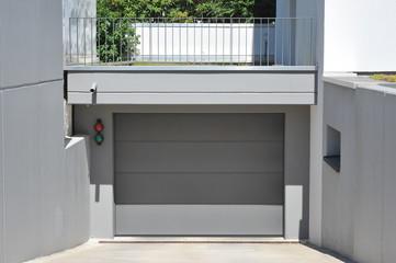 Moderne Einfahrt mit Beton-Wänden und Garage mit Automatik-Tor
