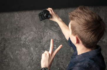 young man photographing himself on the old camera