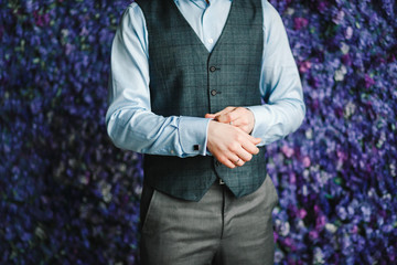 Close up image of a fashion the hands of a young businessman, handsome model man in casual cloth costume. Wearing the vest in the cage, black jeans and blue shirt.