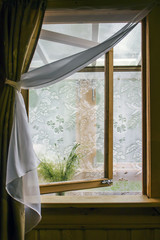 Inner window open to the terrace. Tulle, portieres, bouquet of wildflowers. Country wooden house. Summer mood.